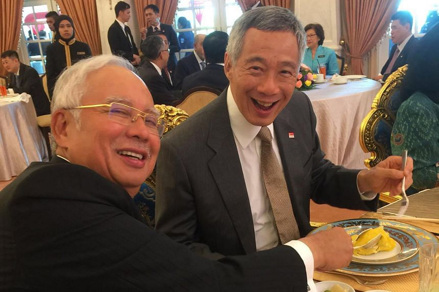 PM Lee and his wife Ho Ching with Mr Najib and his wife Rosmah Mansor, surrounded by the media at the Seri Perdana, the Malaysian Prime Minister's official residence, in Putrajaya yesterday. PM Lee and Mr Najib at yesterday's lunch hosted by the Mala