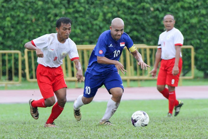 Singapore cerebral palsy captain Khairul Anwar (in blue) with the ball in his side's match against Indonesia at Hougang Stadium yesterday evening. The hosts lost 1-6 and also suffered a 5-0 defeat against Thailand on the same morning in the inaugural