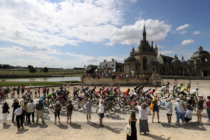 The pack riding past Chantilly Castle at the start of the 113km 21st and last stage of the 103rd Tour de France. Despite the tight security, one of the charms of the race is the ability of fans to get up close to their sporting heroes.