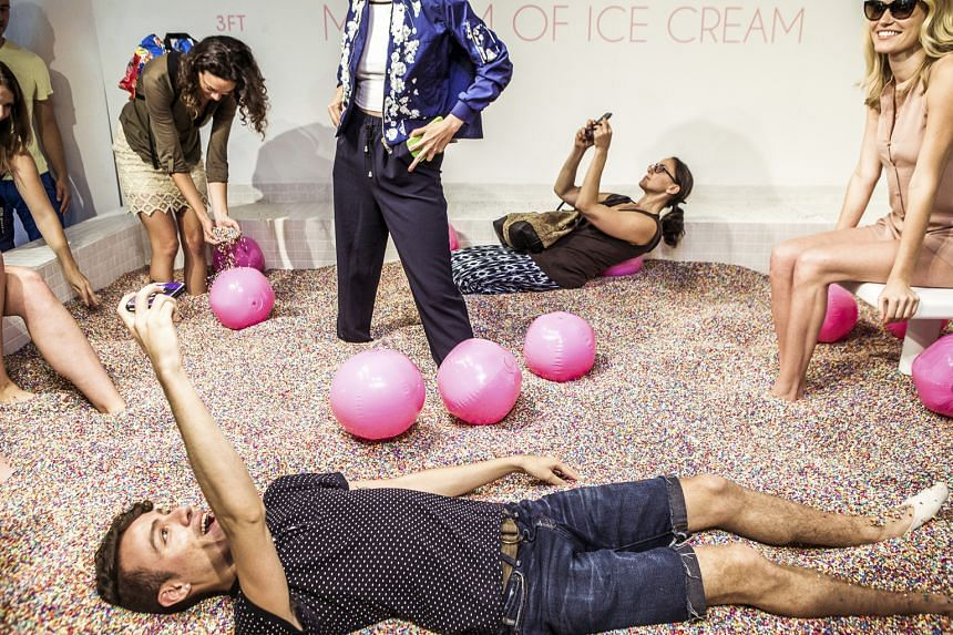 """Visitors play at the Museum of Ice Cream's main attraction - a room with a swimming pool full of rainbow """"sprinkles""""."""