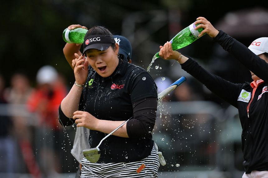 Thailand's Ariya Jutanugarn is sprayed with bottled water after winning the Women's British Open at Woburn Golf Club on Sunday. She avoided a repeat of the ANA Inspiration, where she led before fading.