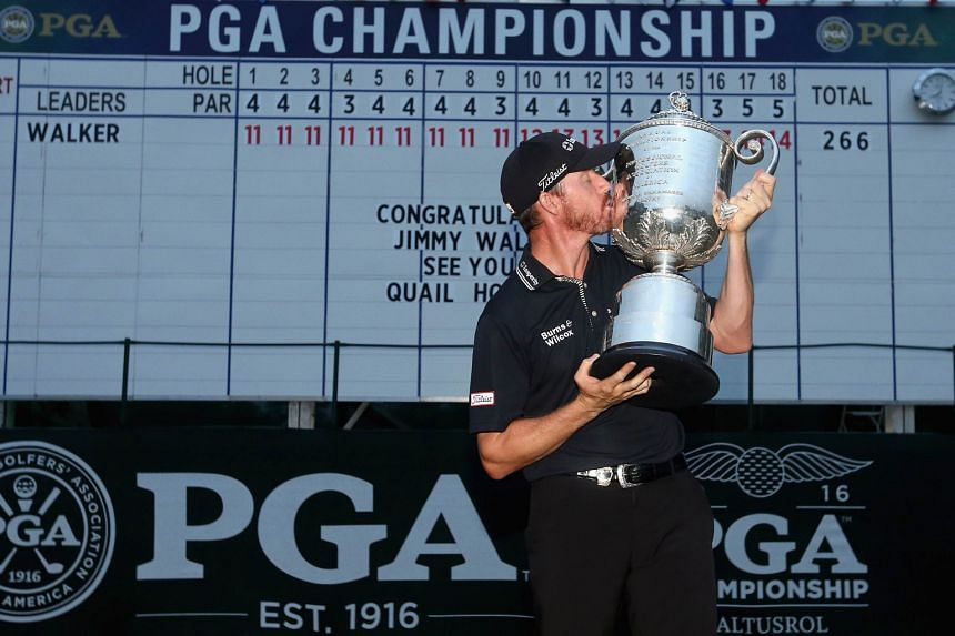 US golfer Jimmy Walker savouring the greatest moment of his career as he lifts the Wanamaker Trophy in front of the leader board, after winning the PGA Championship at Baltusrol Golf Club.