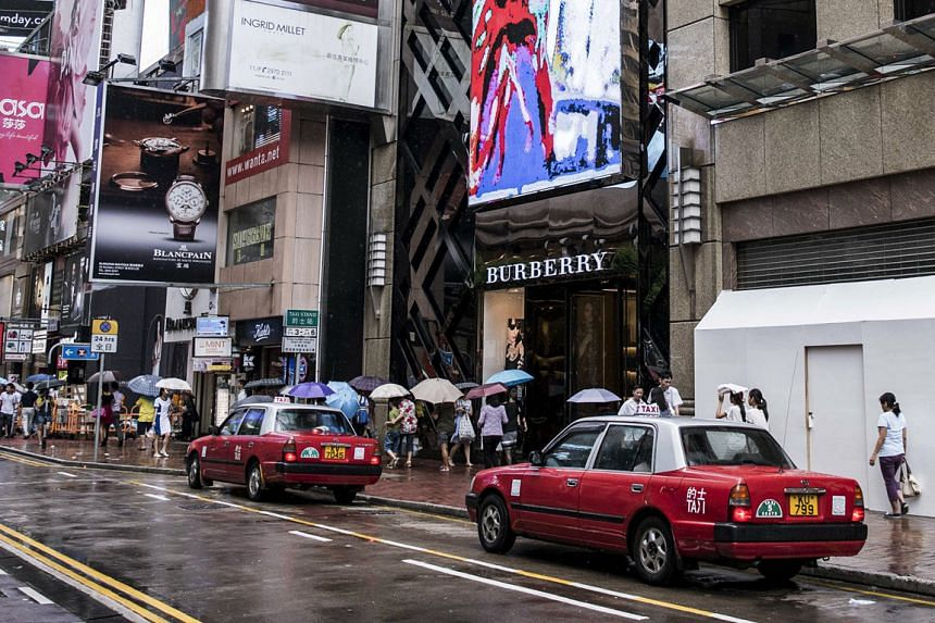 Landlords on Hong Kong's Russell Street (left) in the prime Causeway Bay shopping district are adjusting to lower retail rents.