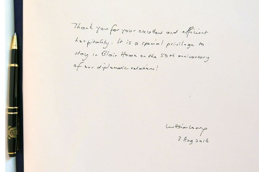 Left: PM Lee leaving this message (above) in the guest book at Blair House, the guest house of the US President. With him were Mrs Lee and Mr Randell Bumgardner, Blair House assistant chief of protocol and general manager.