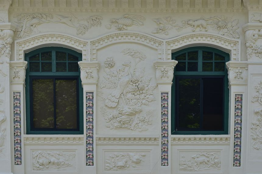 The facade of the two-storey shophouse (main picture) is adorned with strips of ceramic tiles with floral designs (above) as well as plaster work featuring, among other designs, a Sikh guard (left).