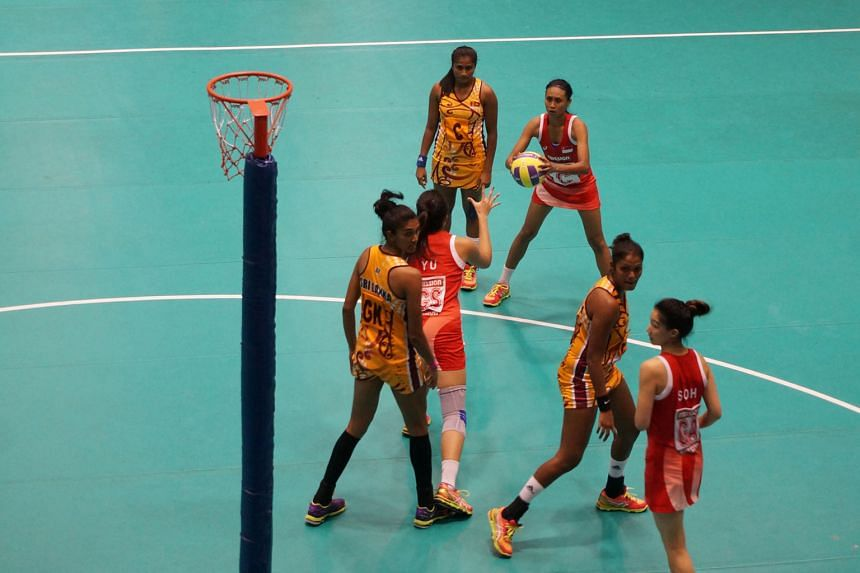 Singapore vice-captain Nurul Baizura (in red) trying to pass the ball to team-mate Yu Meiling during the semi-final of the Asian Netball Championships yesterday. The Republic lost 30-36 to Sri Lanka.