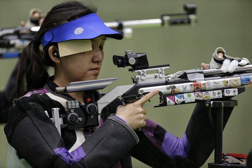 "Jasmine Ser preparing to shoot during the women's 10m air rifle event yesterday. She finished 25th out of 51 competitors with a score of 413.5, but said, ""I'm OK"" while shifting her focus to the 50m three-position event."