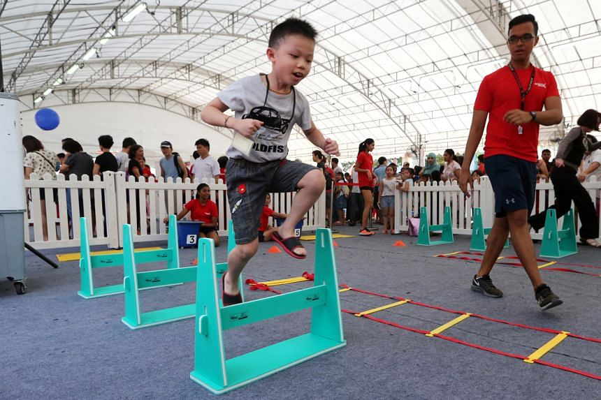 A young athlete clearing some miniature hurdles at the GetActive! Singapore festival yesterday. The event at Jurong East attracted around 18,000 participants.