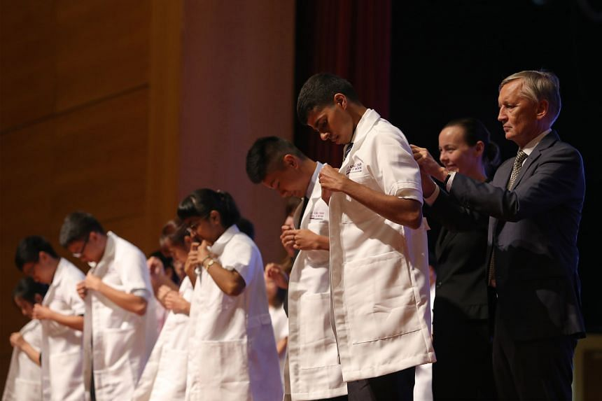 NTU medical students receiving white coats in a special ceremony yesterday. The coats symbolise the knowledge and compassion that they must exercise in the future.