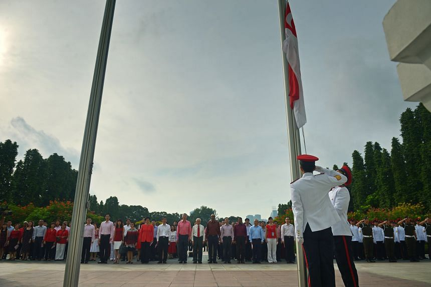Presidential guards preparing for the flag-raising ceremony as staff from the Prime Minister's Office and President's Office gathered for the National Day observance ceremony held at the Istana yesterday. Attendees - including President Tony Tan Keng