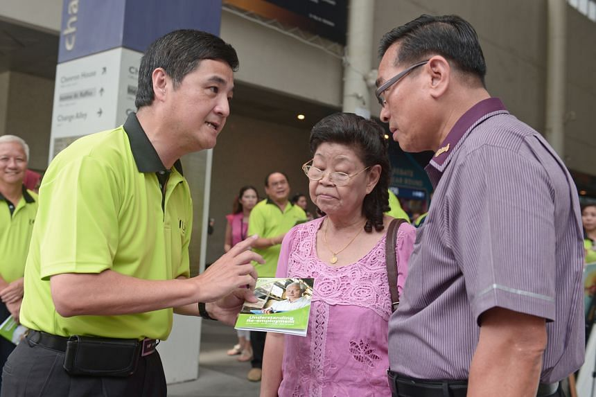 Mr Heng (left) explaining a new NTUC guidebook on re-employment to Madam Sng and Mr Lim Yew Huat, 65, an SBS chief bus captain. The re-employment age will be raised from 65 to 67 from July 1 next year.