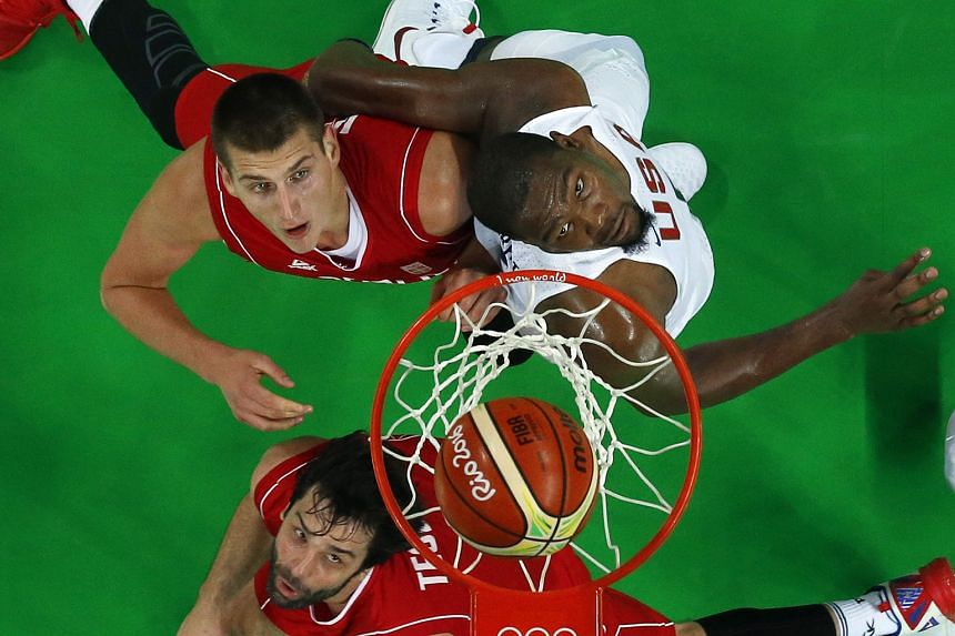 Serbia's Milos Teodosic (bottom) and Nikola Jokic jostling for space with the US' Kevin Durant during their Group A match at the Carioca Arena 1. The Americans edged out Serbia 94-91.
