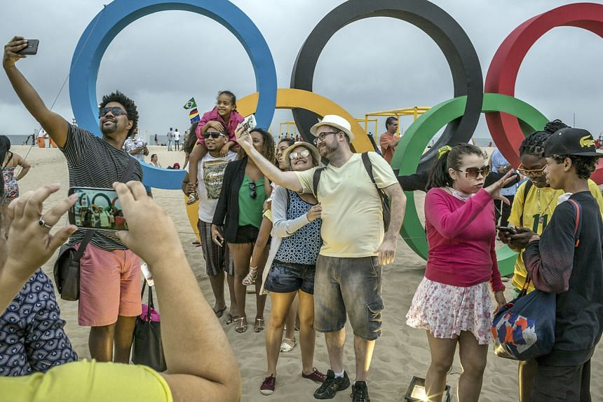 A Brazilian man uses his street cart rigged with a TV to watch the basketball match between Serbia and Australia. Locals and tourists stop by the Olympic rings next to the beach volleyball arena at Copacabana Beach to take photographs. At this arena,