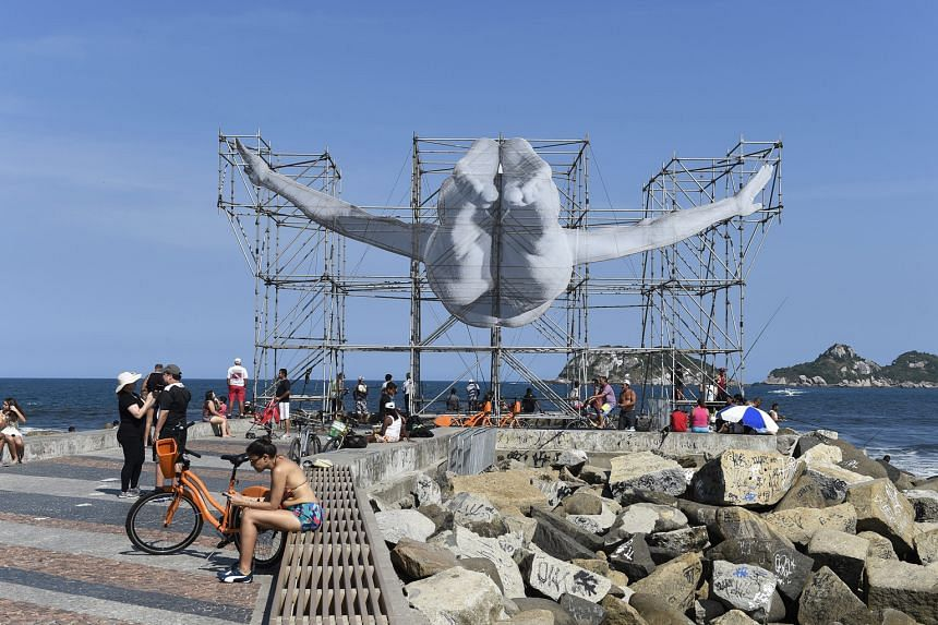 Sculptures by French artist JR depict Brazilian diver Cleuson Lima Do Rosario (above) and Sudanese high jumper Ali Mohd Younes Idriss in Rio de Janeiro.