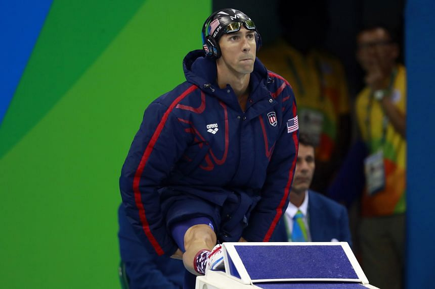 Michael Phelps wearing the US swim team's warm-up parka before the start of the men's 200m butterfly final, in which he won gold, in Rio de Janeiro.
