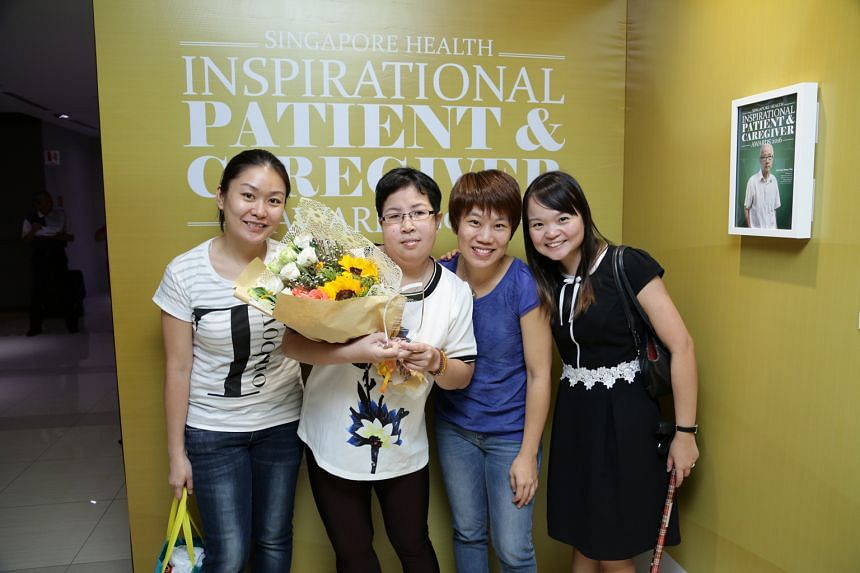 Ms Kwan (holding flowers) with (from left) Ms Zhou, SG Enable manager Tan Bee Hui and Ms Ho. Her positive attitude got her a Singapore Health Inspirational Patient Award nomination.