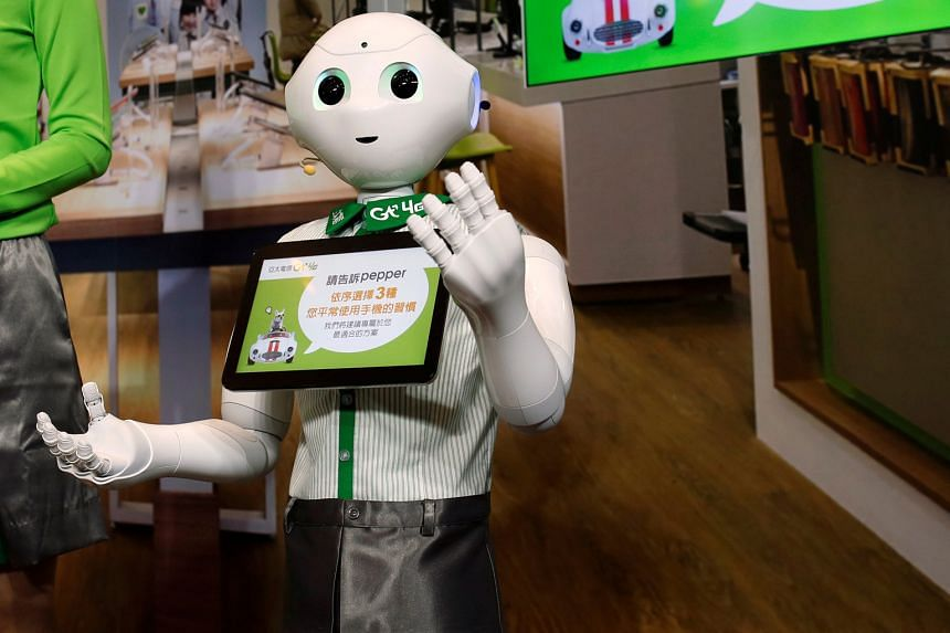"""Japanese firm SoftBank's """"Pepper"""" robot, dressed in an Asia Pacific Telecom uniform, in Taipei."""