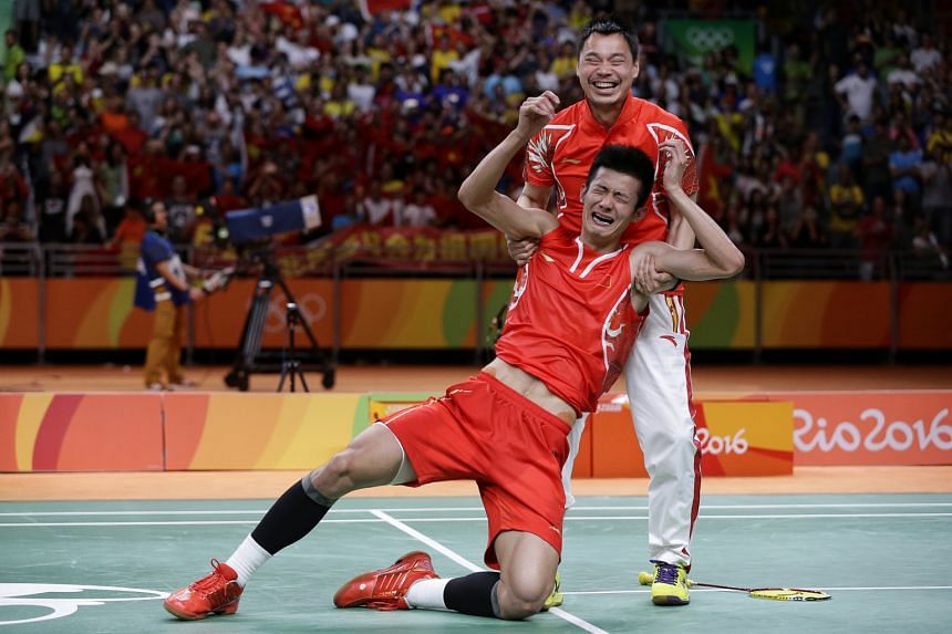 An emotional Chen Long needs to be helped to his feet by his elated coach Xia Xuanze after beating Lee Chong Wei of Malaysia to win the Olympic badminton men's singles gold. It is the 27-year-old's first Olympic singles title and he succeeds his lege