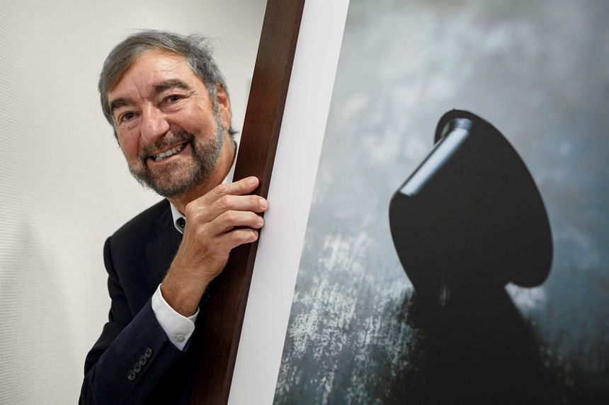 Nespresso inventor Eric Favre with a picture of a coffee capsule.