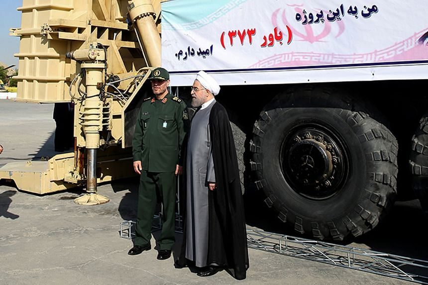 President Hassan Rouhani (right) and Defence Minister Hossein Dehghan standing next to the Bavar 373, Iran's new long-range missile defence system.