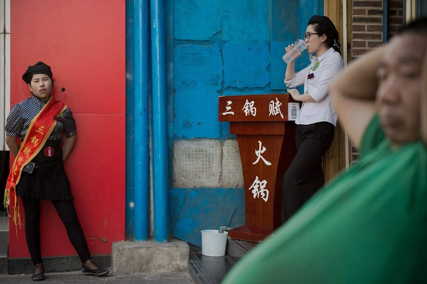 Workers at a restaurant in Beijing waiting to welcome customers. The industrial sector's reluctance to retrench staff slows the shift of labour to service jobs, where demand is stronger.