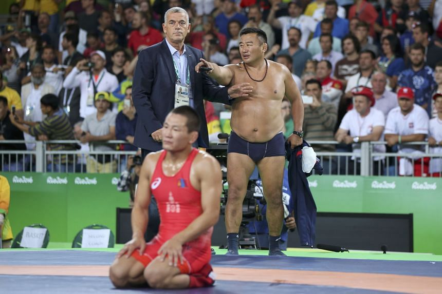 Controversy erupts as a coach of Mongolian wrestler Mandakhnaran Ganzorig (kneeling) strips and argues with the tournament referees, who had judged that Ganzorig should lose his bronze-medal match against Uzbekistan's Ikhtiyor Navruzov.