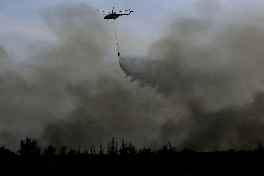 A helicopter dropping water on a fire in Ogan Ilir, near Palembang in South Sumatra, on Aug 11.