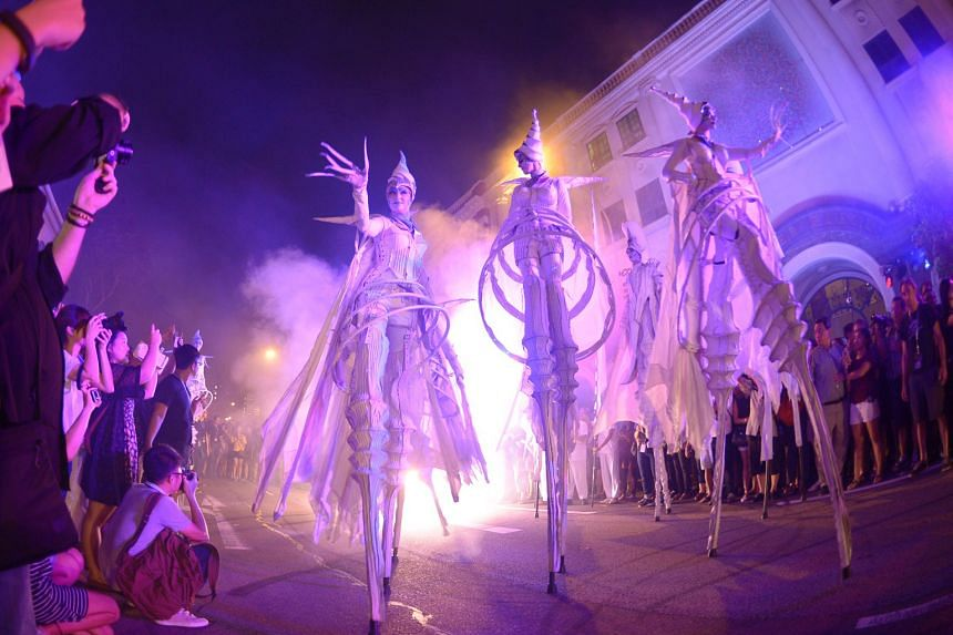 Night Festival goers getting a close-up of silver-suited stilt-walkers from Dutch street theatre group Close-Act as they paraded down Armenian Street yesterday. While showing off thrilling acrobatics, the street entertainers led the crowd towards the