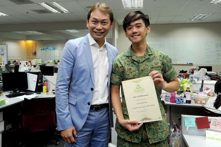 Sakae founder and chairman Mr Foo (at left) with marketing executive Mr Lee. Sakae staff who are NSmen receive vouchers for performing their NS duties well. Mr Lee received a certificate and an $80 voucher from the firm for getting a Silver in his IP