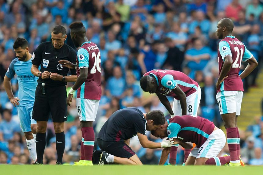 West Ham's Winston Reid (on ground) receiving treatment from a physiotherapist after a clash with Aguero.
