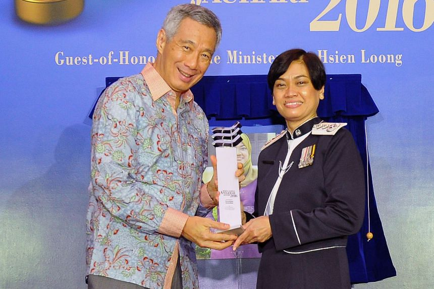 Madam Zuraidah receiving her award from PM Lee yesterday. Her accomplishments include being the first woman to become Senior Assistant Commissioner in the police force.