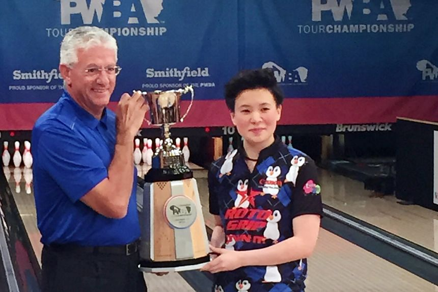 Singapore bowler New Hui Fen receiving the prestigious Smithfield PWBA Tour Championship trophy yesterday, after defeating compatriot Cherie Tan 258-235 in the final. New was also the Rookie of the Year.
