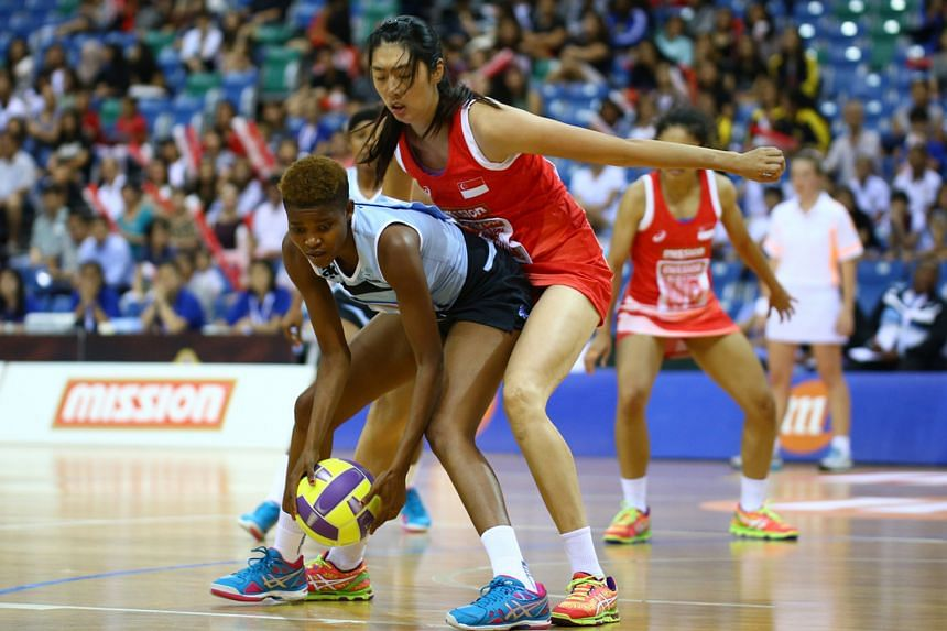 """Botswana shooter Hildah Binang receiving a low pass while marked by Singapore goalkeeper Chen Lili. Botswana won 42-38 after establishing a 12-7 lead at the end of the opening quarter and coach Sithulile Mhlotshwa said: """"""""Hildah was one of the key re"""