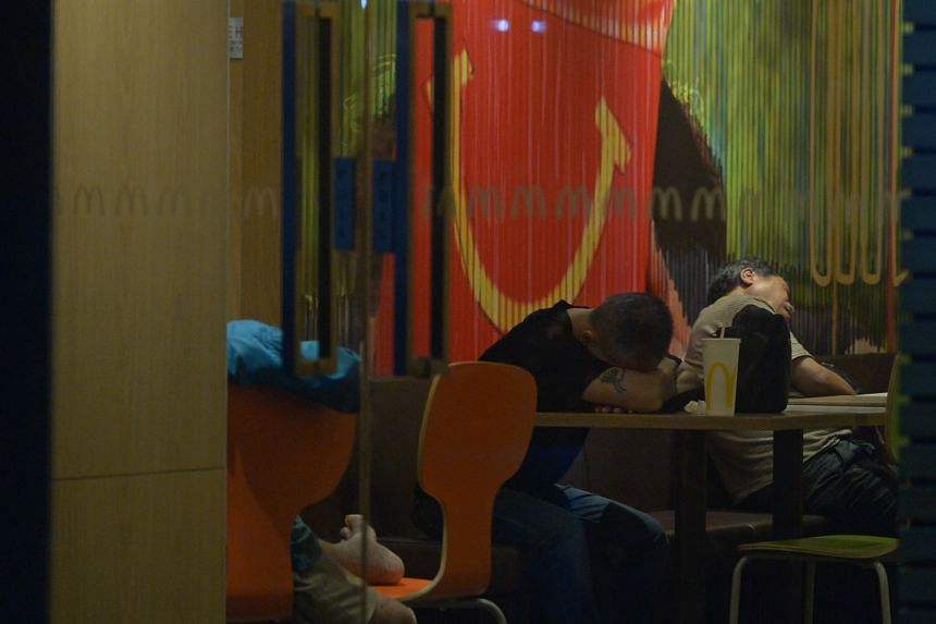 Top and above: Patrons at a McDonald's outlet in the southern part of Singapore early yesterday morning. Some seek respite in the air- conditioned outlets while others find it hard to sleep at home.