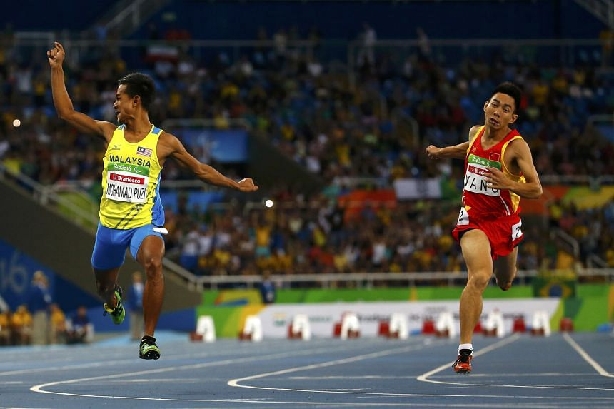 Mohamad Ridzuan Mohamad Puzi of Malaysia (left) wins gold in the 100m T36 after crossing the line in 12.07 seconds. Yang Yifei of China took silver.