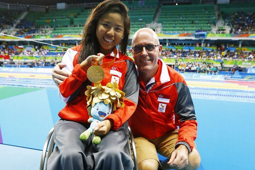 Singapore's Yip Pin Xiu celebrates winning the gold medal in the 100m backstroke S2 event at the Rio Paralympics. Because she has muscular dystrophy, her coach Mick Massey, beside her, has to lower her into the pool and hold her hands as she can no l