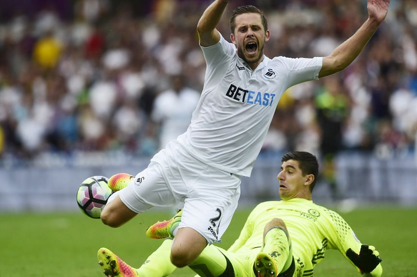 Swansea's Gylfi Sigurdsson is fouled by Chelsea's Thibaut Courtois, resulting in a penalty that the midfielder put away in a 2-2 draw. Chelsea coach Antonio Conte was aggrieved at a number of fouls Swansea's players had committed that went unpunished