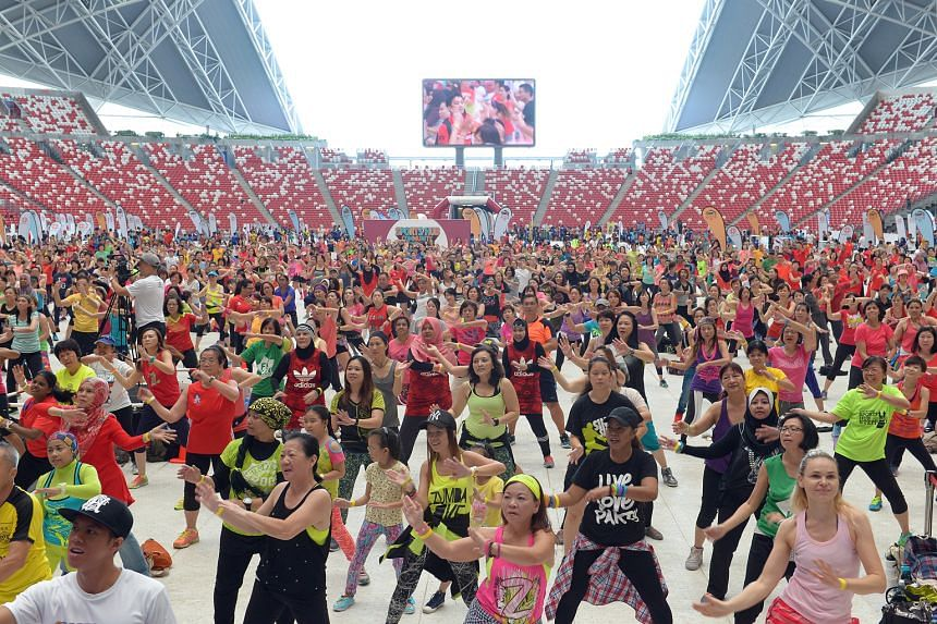 From top: Thousands of Zumba enthusiasts performing dance sequences together at the National Stadium pitch yesterday morning. Great Eastern mascot Sunny and participants of the Great Eastern Women's Run taking part in the Zumba event. They were invit