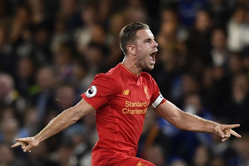 Liverpool captain Jordan Henderson celebrates scoring Liverpool's second goal at Stamford Bridge on Friday. The visitors beat Chelsea 2-1, adding to key victories against Arsenal and reigning champions Leicester City this season.