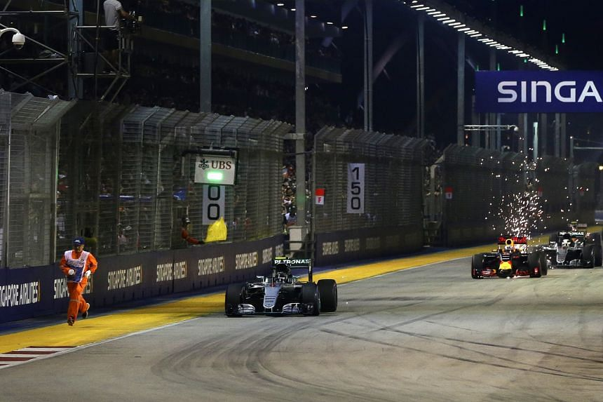 A safety steward running on the side of the track, as the Mercedes of eventual winner Nico Rosberg powers ahead towards Turn 1 at the restart of the race.