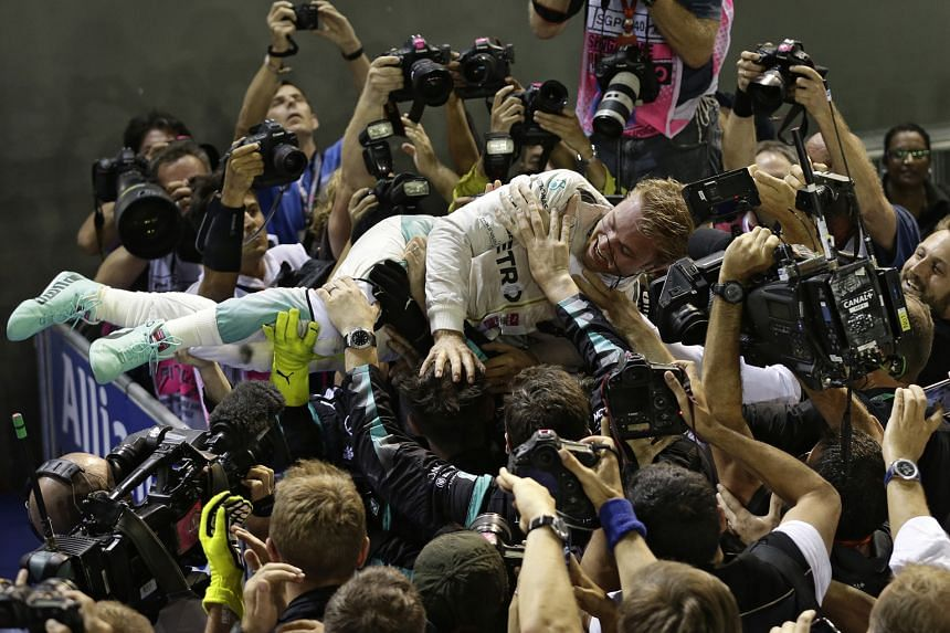 Mercedes driver Nico Rosberg celebrating with his team after winning the Singapore Grand Prix at the Marina Bay Street Circuit. It was the German's third race win in a row.