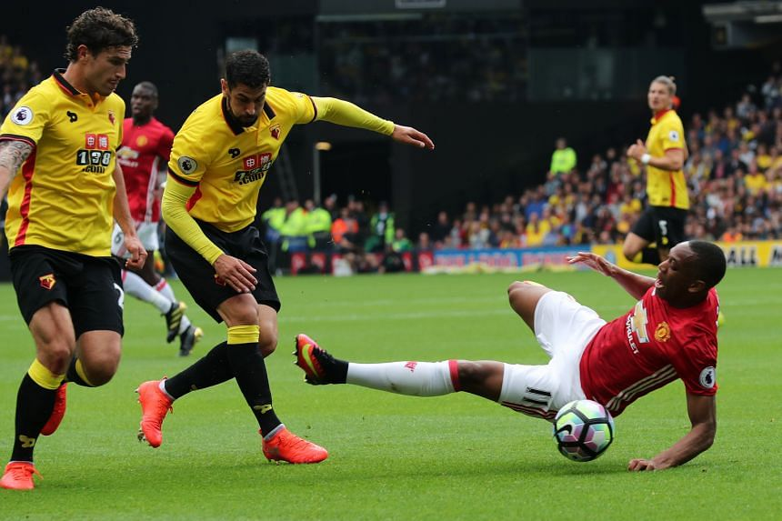 Manchester United forward Anthony Martial (right) is challenged by Watford defender Miguel Britos (centre) before Etienne Capoue (not pictured) scores the opener. United manager Jose Mourinho claims United should have been awarded a free kick for the