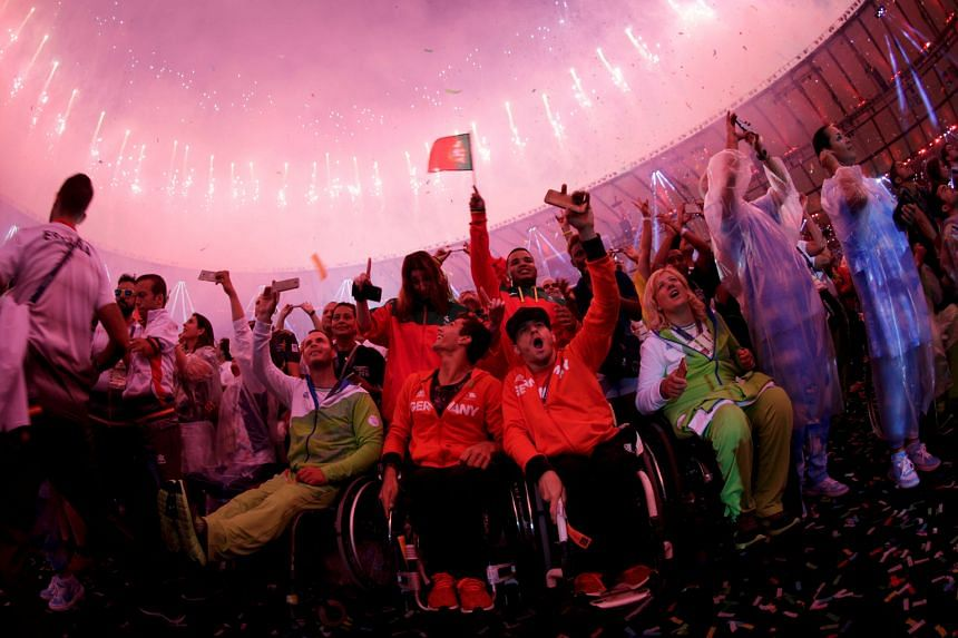 Athletes from various countries soaking up the atmosphere while fireworks erupt during the closing ceremony.