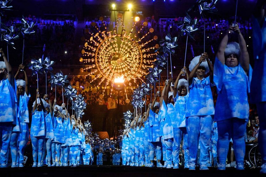 Dancers performing with the Rio cauldron – based on a kinetic wind sculpture – dominating the background.