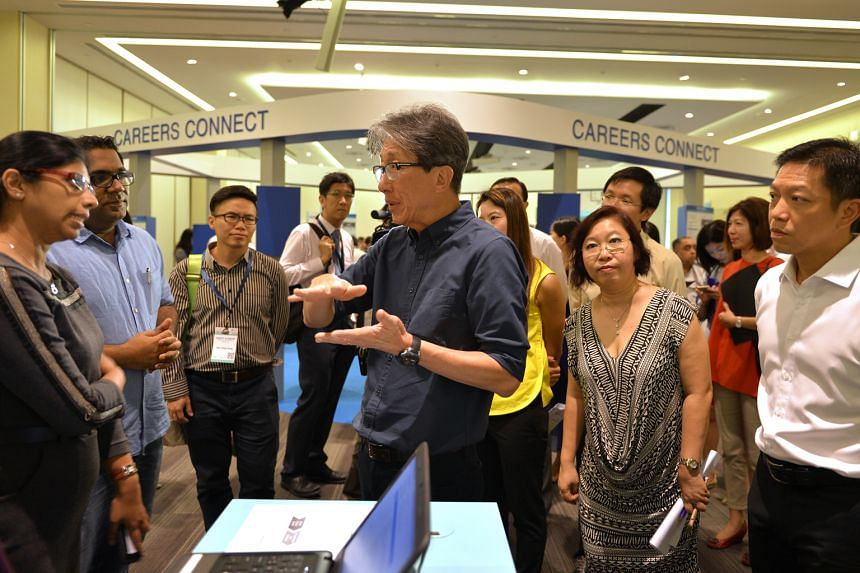 Manpower Minister Lim Swee Say (centre) speaking to employees of Optimum Solutions, which is looking to hire staff, during his visit to the Adapt And Grow Virtual Career Fair earlier this month. The fair is a pilot project by the Singapore Workforce