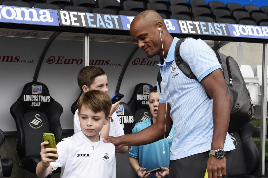 Manchester City's Vincent Kompany engaging young Swansea fans before their Premier League game on Saturday. His latest spell on the sidelines came when he was hurt during the two sides' League Cup tie in midweek.