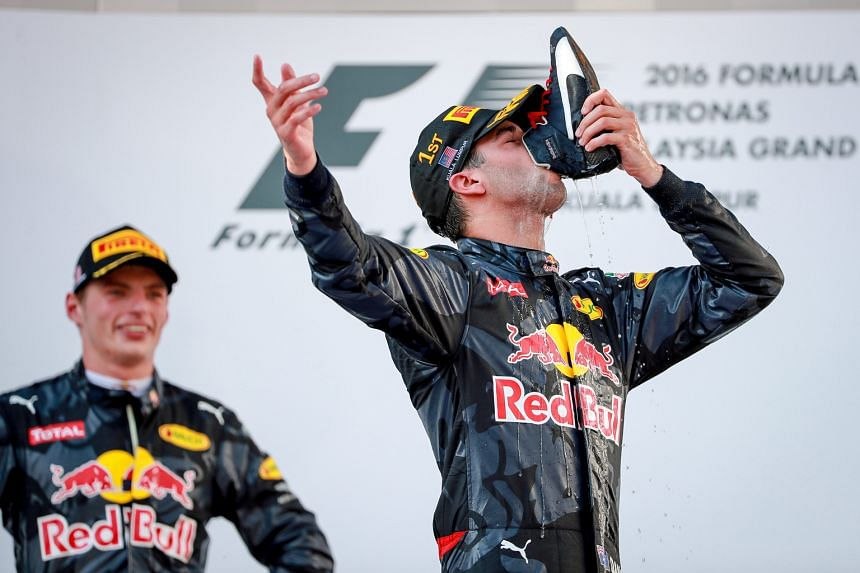 Malaysia Grand Prix winner Daniel Ricciardo marks his first race win this year by drinking champagne out of his boot, as second-placed team-mate Max Verstappen watches.