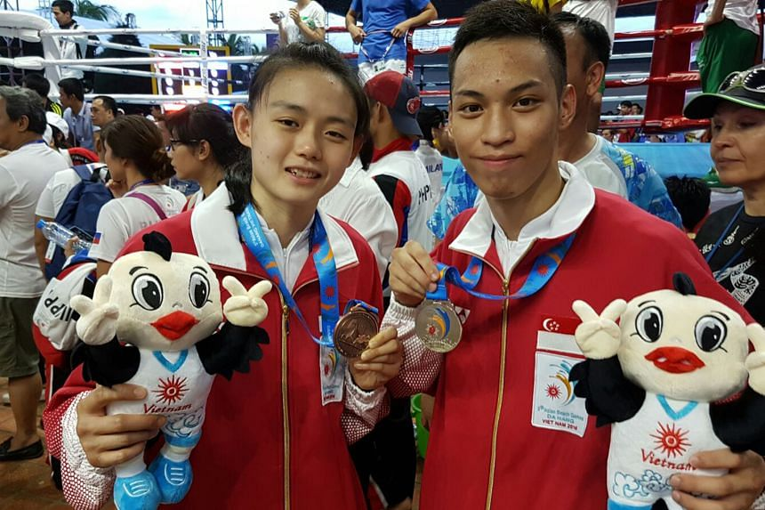 Above: Singapore's muay thai fighters Cheryl Gwa (left) and Bryant Tee show off their Asian Beach Games medals.