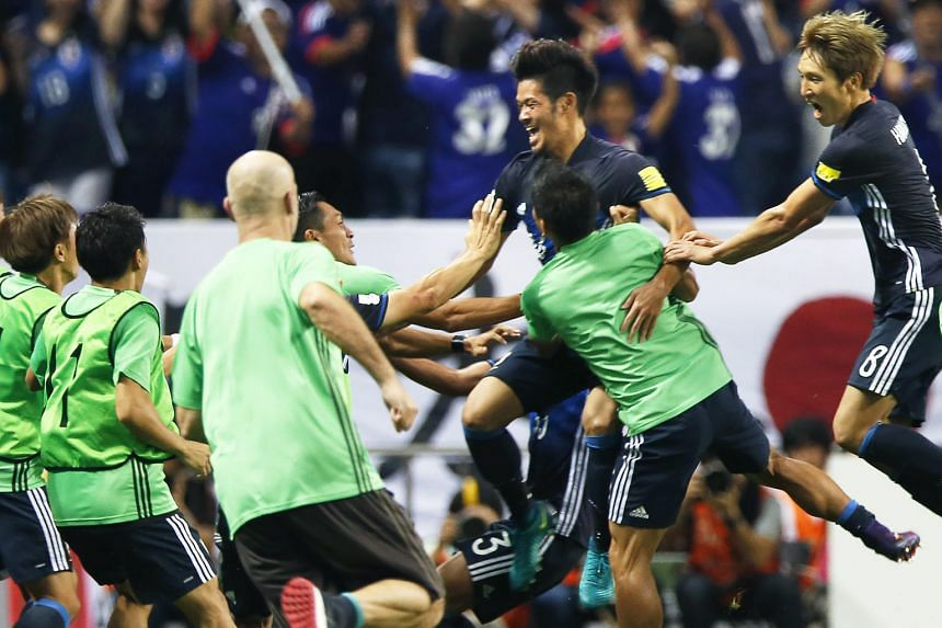 Japan midfielder Hotaru Yamaguchi (third from right) celebrates with his team-mates, including Genki Haraguchi (extreme right), after scoring a late winner during their World Cup qualifier against Iraq.