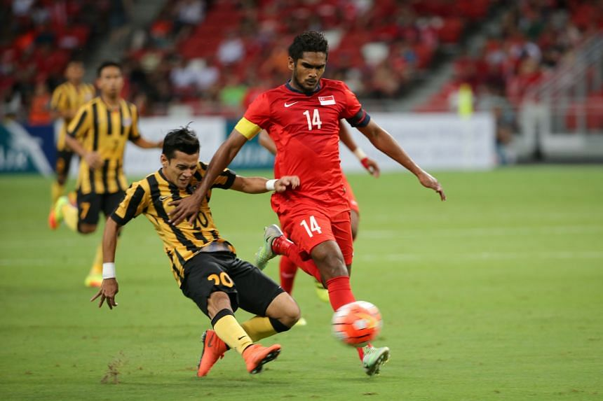 Hariss Harun being challenged by Malaysia's Azrif Nasrulhaq during last Friday's 0-0 draw. Hong Kong should prove to be a tougher proposition tonight.
